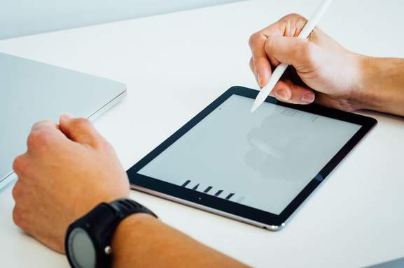 a man writing with an apple pen on an ipad