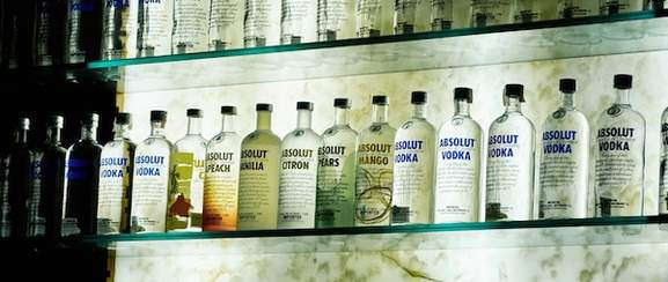 A row of absolut vodka bottle on shelf