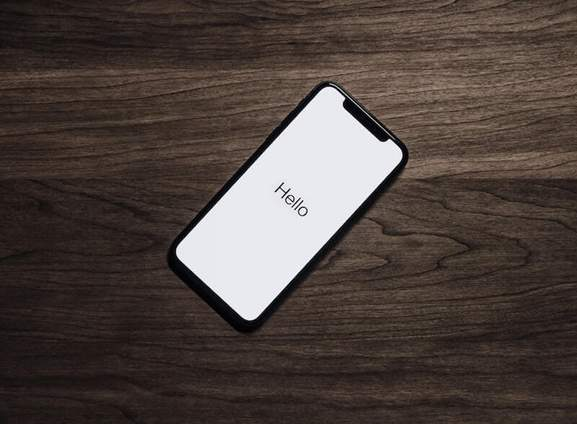 iPhone on table with text 'hello'