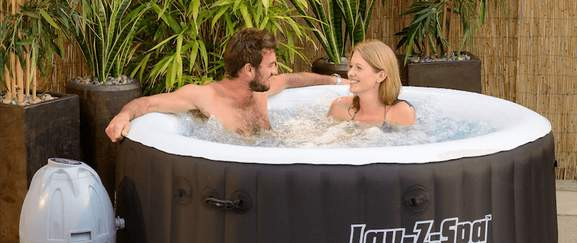 man and woman sitting in a lay-z spa