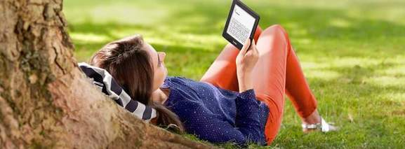 woman reading kindle paperwhite in the park