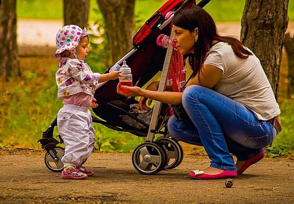 mom gives baby girl something to drink while standing in front of a pushchair