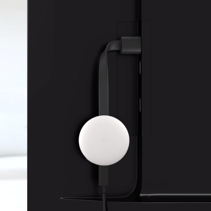 Google Chromecast white plugged into TV