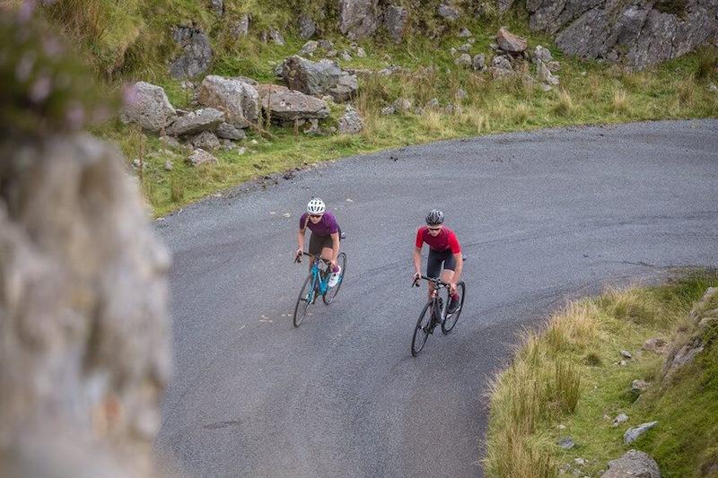 two bikers biking up the road