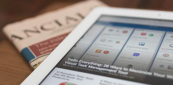white ipad air on top of a newspaper