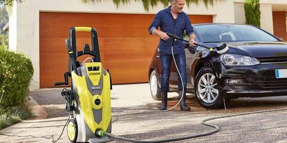 man washing his car outdoors with a vax pressure washer