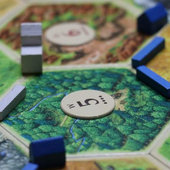 Settlers of Catan blue and white game pieces on board with number 5