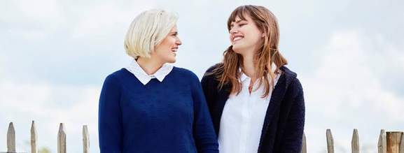 a blond girl in a blue sweater and a brunette in a button down laughing together