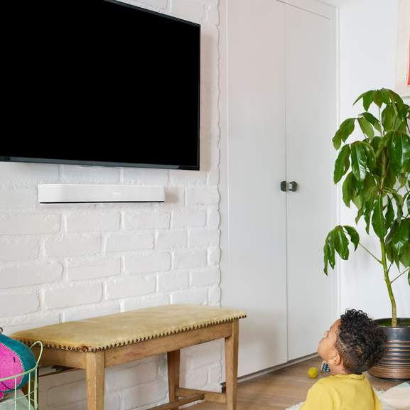 Boy watching tv with sonos beam on wall mount underneath