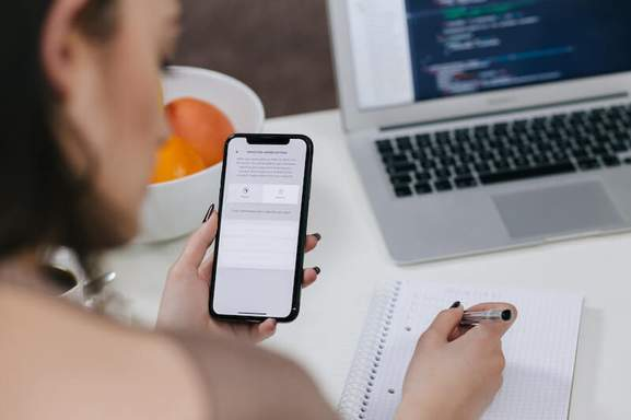 women holding space gray iphone x and black pen in front of a blurred laptop background