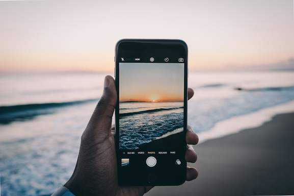 man is taking a photo of a beach with an otstretched hand