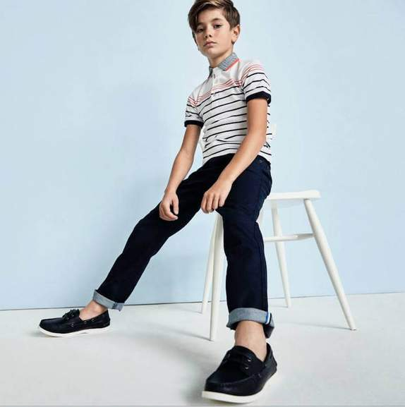 boy sitting on a stool wearing striped shirt and rinsed jeans