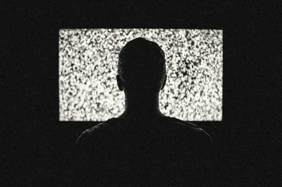 man watching tv in a very dark room