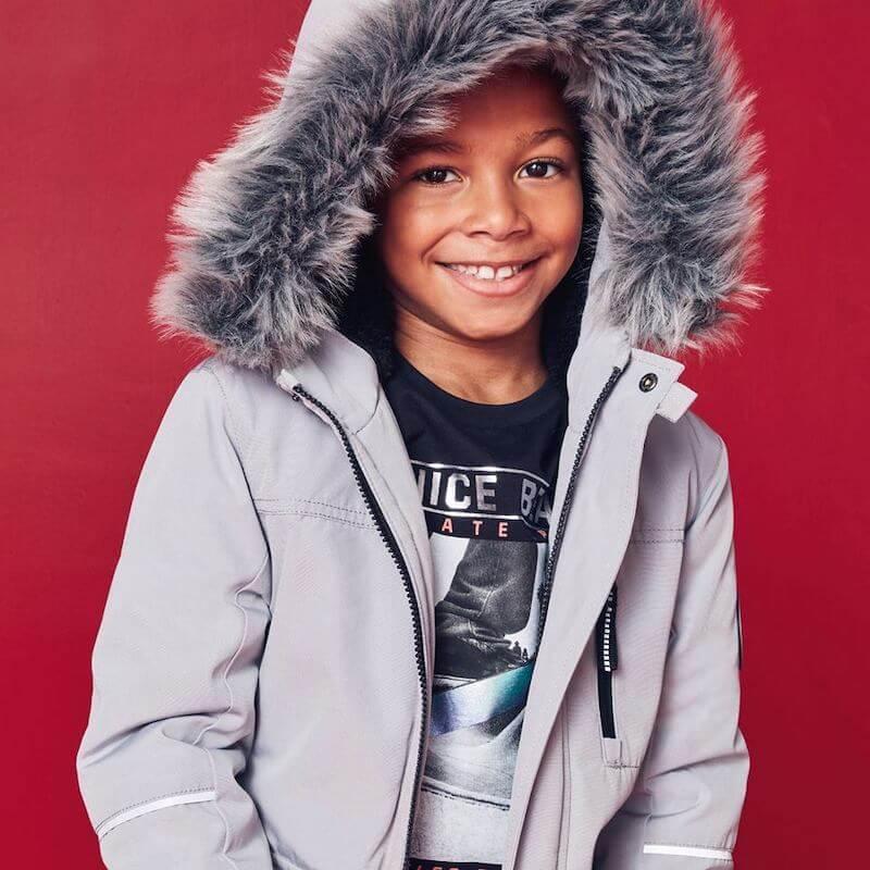 Boy wearing grey coat with fluffy hood