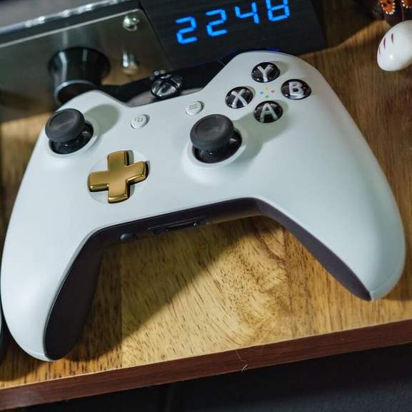 Customised Xbox One controller in white, black and gold next to digital clock