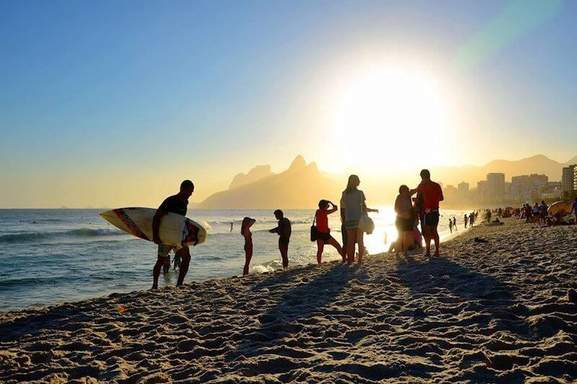 a bunch of people with surfboards and swimming things at a beach