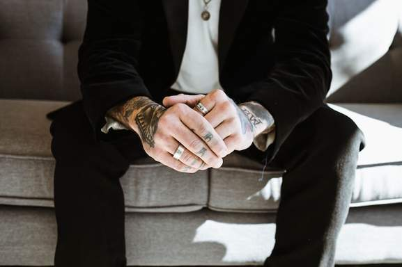 close-up of a tattooed man's hands wearing rings, a necklace and a suit