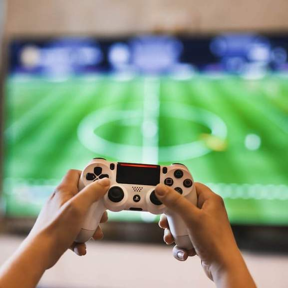 Playstation controller white in front of fifa on tv
