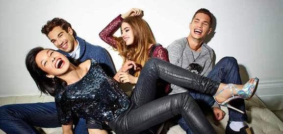 two girls and two guys wearing USC party attire laughing at a party