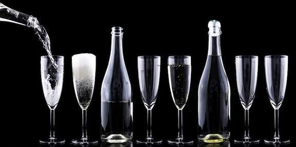 champagne bottles and flutes standing in a row with a dark background