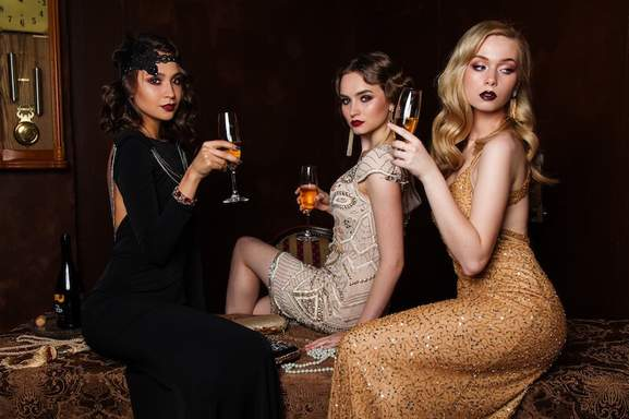 three classic styled woman sit and drinking champagne