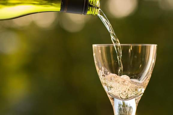 serving a glass of white wine with a blurred background