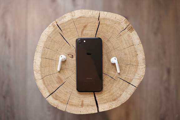 AirPods next to black iPhone on tree stump