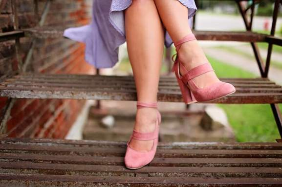 adult female sitting on stairs and wearing pink heels