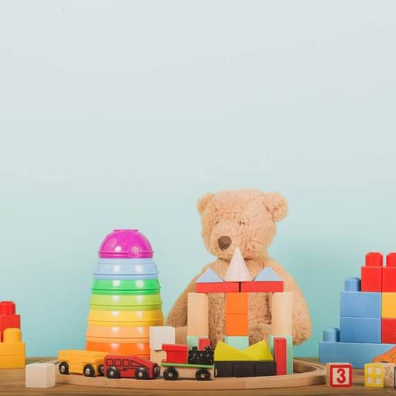 Wooden trains, soft cuddly bear, and other toys in front of sky blue background