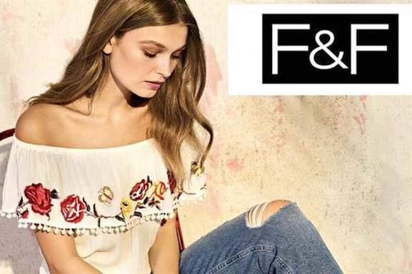Woman wearing off the shoulder top next to F&F clothing logo