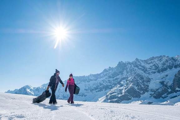 man and woman are carrying bags in a winter mountain setting