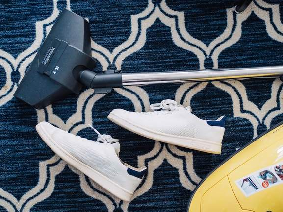 vacuum cleaner from miele lying on a blue patterned carpet next to a pair of adidas stan smith sneakers