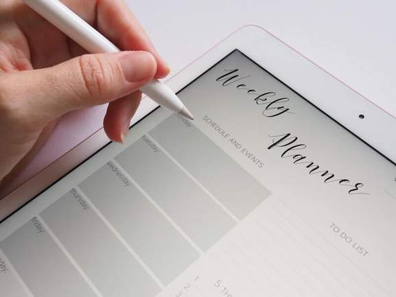 person writing with an apple pencil on the ipad pro