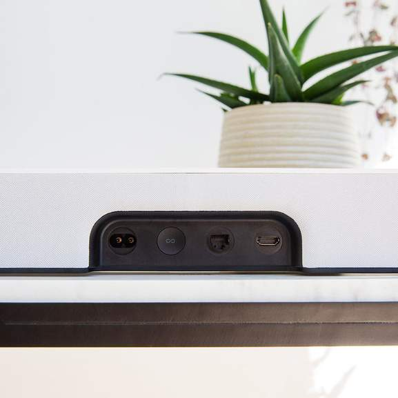 Plant behind the back of white Sonos Beam showing connections