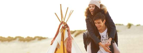 a piggybacked couple by the beach with a tent