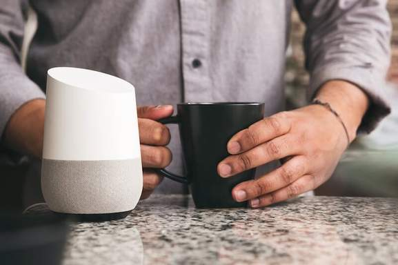 Google Home white next to person holding coffee mug