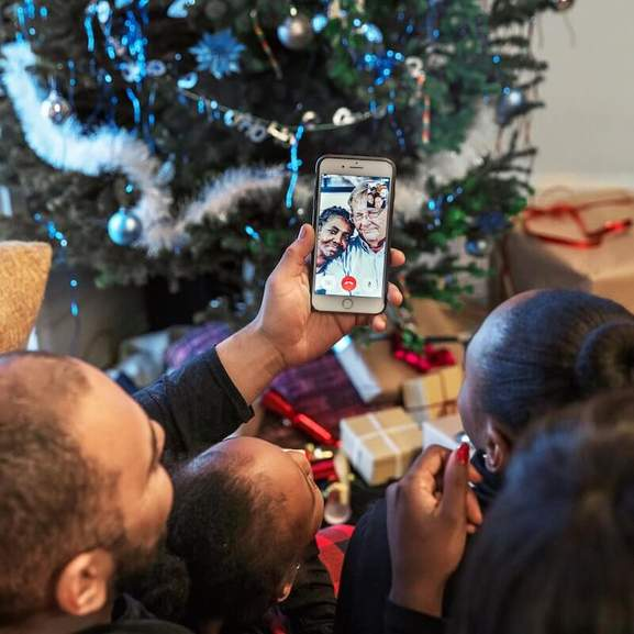 Family video calling grandparents on phone in front of christmas tree