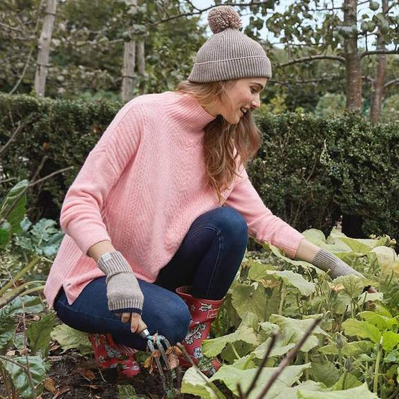 a woman in a pink sweater and jeans working in a garden