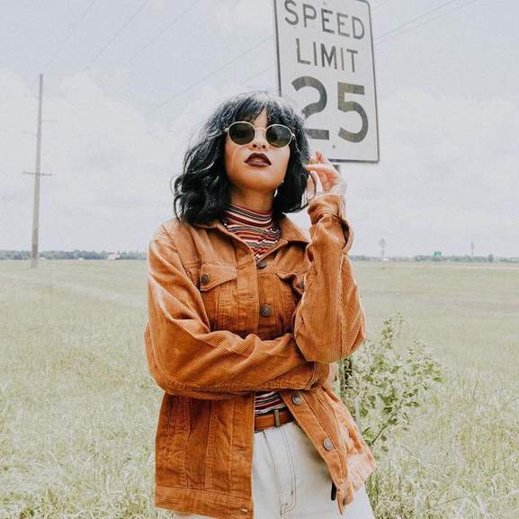 woman in corduroy jacket and black sunglasses standing in front of a speed limit 25 sign