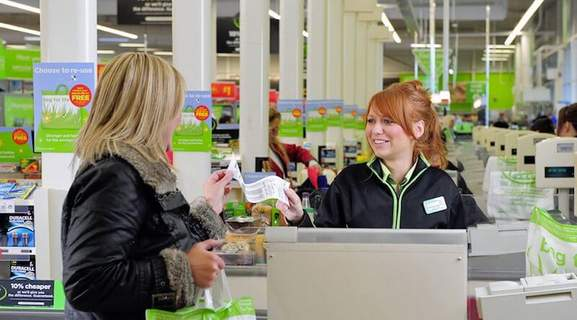 asda woman with red hair is serving a female customer in one of their supermarkets