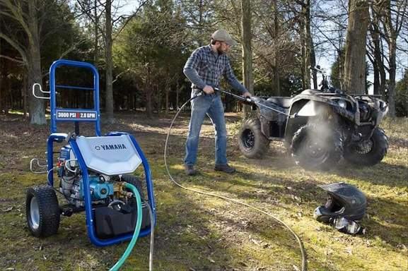 a man cleans his quad with a yamaha pressure washer