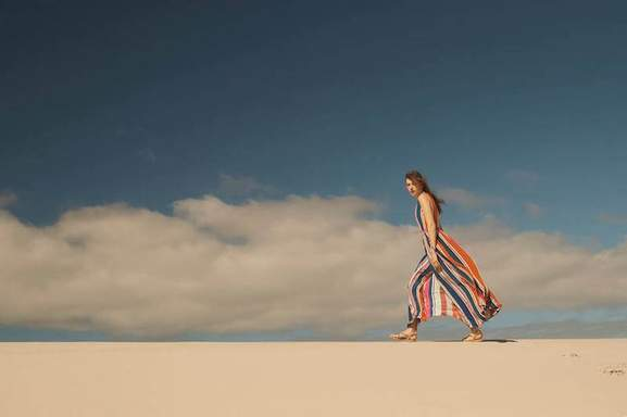woman with a striped monsoon dress and sandals takes a walk at the beach