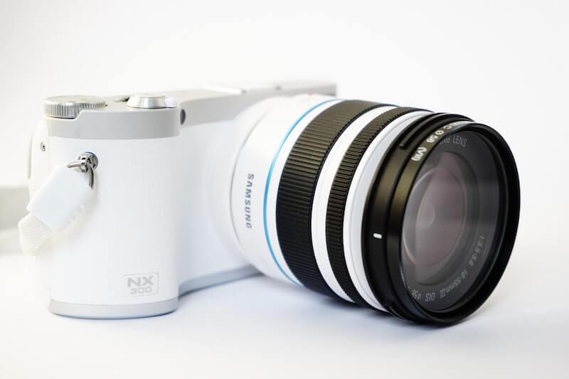 White and Black Samsung Nx 300 Dslr Camera on White Surface