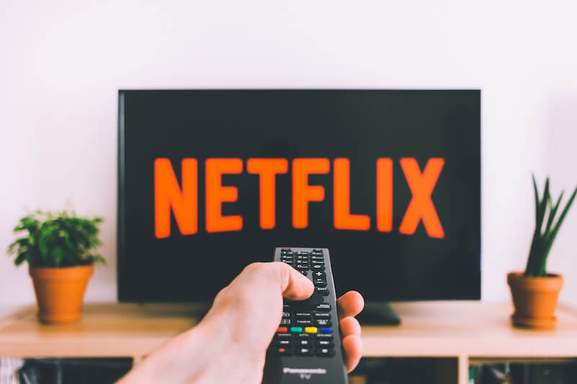close-up of male hand holding a remote control turning on netflix on a tv