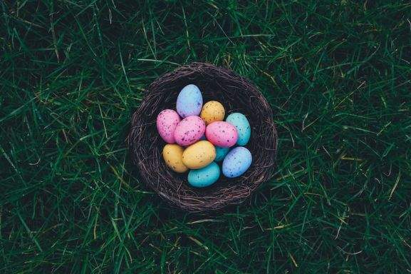 easter eggs in a basket lying on a lawn