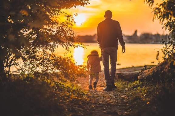 father and his child are taking a walk at a lake in the sunset