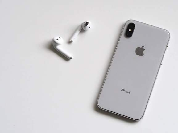 AirPods next to silver iPhone