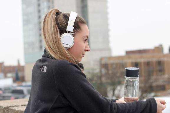 woman with a water bottle in hand is wearing white headphones in an urban environment