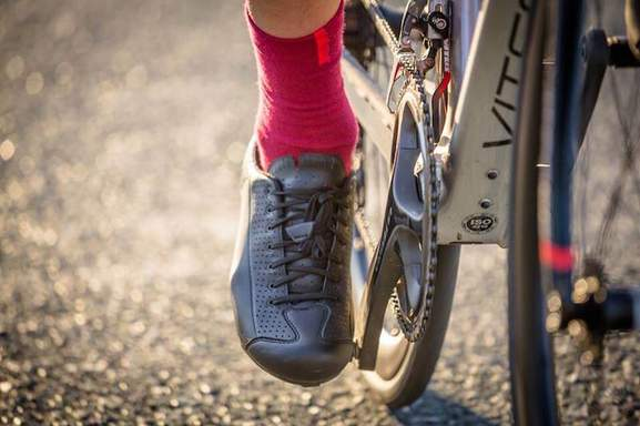 close up image of a black biking show a red sock