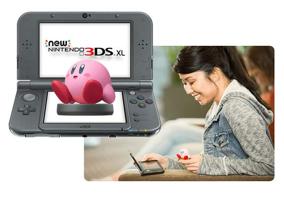 woman playing with an amiibo of kirby on the nintendo 3ds gaming console